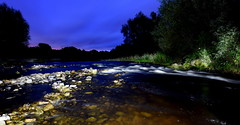 Time To Shine (Peter.S.Roberts) Tags: interestingness interesting river riverelwy stasaph north wales northwales elwy water stones movement motion landscape waterscape bank riverbank longexposure night summer outdoor 26082017 flowers reeds plantlife foliage leaves greenery vegitation trees blue bluehour rocks light illumination timetoshine shadows dark welsh cymru shrubs riverscape flowing biota waves rapids lighting clear transparent pellucid grass fourminuteexposure flora perspective pov dof quiet peaceful tranquil relaxing calming serene riverscene scenic beautiful mesmerising