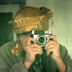 reflected self-portrait with Balda Baldessa-F camera and plush yellow hat (square crop) (pho-Tony) Tags: square cameraselfportraits baldessaf balda baldabaldessaf prontor 125 prontor125 isconar 128 f28 45mm 35mm film isco colorisconar baldessa german germany 1960s agfa vista poundland rollei digibase c41 exhaused failure underdeveloped exhausedchemicals