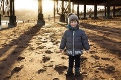 A glorious afternoon in Teignmouth (Christian Hacker) Tags: child son teignmouth devon pier pillars sun sunlight blaze golden sand beach coast coastal england canon50d tamron handheld january dayout fun smile smiling parka cap footprints red cheeks children boy backlight scarf water sea back urban space waterfront stroll strolling dog walking sheldon scaffold framework arcade posing portrait standing cheeky shadow light bobble wee little stake stakes pole poles velcro winter
