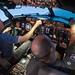 Secretary of the Navy pilots a flight simulator of a P-8A Poseidon aircraft.