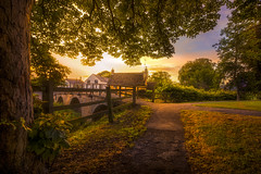 Take A Walk (unciepaul) Tags: medbourne village church grounds trees path sunset summer warmth calm tranquil peacefulness glow colours house bridge grass nikond800 tripod lightroom one image cloned power line out must re visit soon walk evening
