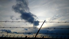 Moody Sky (Georgie_grrl) Tags: clouds ttc fromthesubway commutehome barbedwire fence toronto ontario