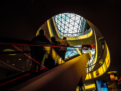 Rise to the brightest peak (A. Yousuf Kurniawan) Tags: bright mall silhoutte people escalator shadow contrast streetphotography urbanlife architecture interior colourstreetphotography yellow light diagonal redline decisivemoment frankfurt hdr