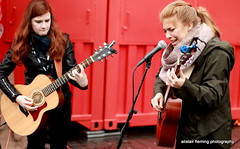 IMG_5656 Street Musicians (marinbiker 1961) Tags: artists musicians guitars acoustic guitarlove female girls redhaed blonde scarf redcontainer virgin music concert guitar