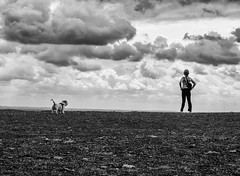 Walk with dog (Georgie Pauwels) Tags: streetphotography public dog women sky clouds moment candid wide fujifilm blackandwhite weather wind