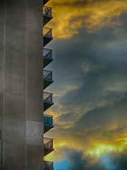 High-rise against a cloudy sunset (duaneschermerhorn) Tags: highrise building structure apartments apartmentbuilding architecture architect concrete balcony balconies dramaticsky sunset yellow blue gray abstract abstraction dramaticclouds clouds