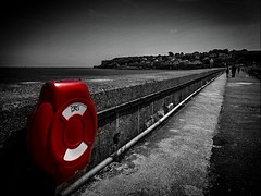 Departition From Colour or 'Sans Couleur' (Rae de Galles) Tags: leadinglines summer concrete rail walk coastal coast britain uk mountain wave waves tourists walking people skies greyscale blackandwhite red saturation colour lifebuoy safety harbour breakwater water sea beach
