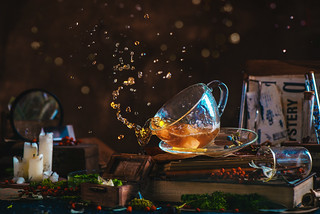 Tea splash in a glass cup on a wooden background with candles, mystery newspaper clips, books, leaves and moss. Tea drops bokeh.