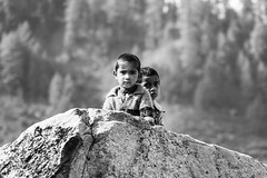 The Shy and the Curious (PB2_2117) (Param-Roving-Photog) Tags: kids children rock forest innocence curiosity shy village rural tirthan himachal unexplored india streetphotography travel monochome blackandwhite bw nikon tamron