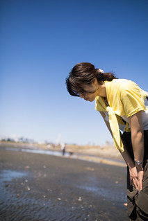 Woman looking for small creatures at low tide on beach
