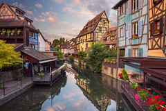 Colmar. (Rudi1976) Tags: colmar france cityscape architecture twilight canal bridge sunrise medieval oldtown traveldestinations famousplace archbridge flowers locallandmark nationallandmark europe downtowndistrict dramaticsky street urbanskyline cloud reflection buildingexterior facade houses