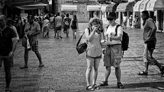Indiana Jones And The Ice Cream Photographer (Alfred Grupstra) Tags: people blackandwhite urbanscene street crowd citylife walking men editorial city outdoors women groupofpeople crowded pedestrian tourist montenegro kotor icecream photography oldtown