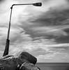 Lamp Post (Karl Johan) Tags: sweden sverige malmö limhamn skåne hasselblad500cm hasselblad 500cm 6x6 mf mediumformat fujineopanacros fuji neopan acros film analog blackandwhite blackwhite rodinal bw ishootfilm epsonv600 epson v600 bwfp monochrome classicblackwhite distagon504fle distagon 504 fle cf 120 outdoor sea ocean stones lamp rocks clouds