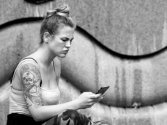 Rebel - with a Cause and a Call (d_t_vos) Tags: woman youngwoman teenager teen portrait street streetportrait beate rebel cause iphone cell cellphone watching candid moody disgruntled piqued blond blonde tanktop cleavage tattoo arm shoulder deathshead skull rose diamond bra wall fountain streetphotography outside outdoor contrast bun irritated curve curves monochrome belin weltkugelbrunnen wasserklops tauentzienstrasse kurfürstendamm budapesterstrasse zwartwit schwarzweiss dickvos dtvos