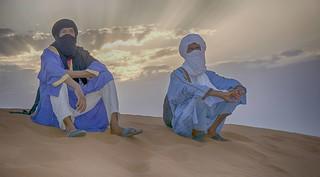 Tuareg men sitting on sand at sunset