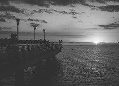 People on the pier. (Pablin79) Tags: sky sunset people water river light clouds outdoor white horizon pier monochrome black shore marina shadows waterfront afternoon argentina silhouettes wharf jetty pontoon peir landing stage pontile misiones foreshore beach posadas