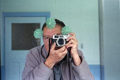 reflected self-portrait with Canonet 28 camera and green parasols (pho-Tony) Tags: cameraselfportraits canonet28 canonet 28 canon rangefinder compact automatic 35mm japan japanese f28 40mm 128 f40mm canoninc canonlens agfavista agfa vista iso 200 film poundland tetenal c41