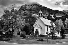 A White Church, Homes and a Mountain Backdrop (Black & White, Yoho National Park) (thor_mark ) Tags: 1stave banfflakelouisecorearea blackwhite bowrange canadianrockies canvas capturenx2edited church cities colorefexpro day3 evergreens fieldbritishcolumbia hillsideoftrees hillsides homes landscape lookingeast mountstephen mountains mountainsindistance mountainsoffindistance mountainside nikond800e outside overcast portfolio project365 rockymountains silverefexpro2 southerncontinentalranges street trees triptoalbertaandbritishcolumbia walkingaroundfield walkingaroundfieldbc whitechurch yards yohonationalpark field britishcolumbia canada