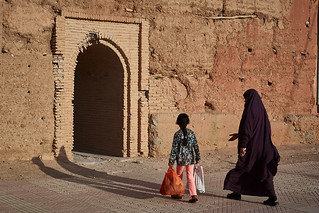 Morrocan veiled woman and little girl walking to fortification door, Taroudant, Morocco