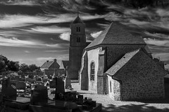 L'église Saint-Martin (Christian Hacker) Tags: léglisesaintmartin vauville church normandy france marche canon50d tamron holiday blackandwhite mono monochrome bw sunny summer graveyard building catholic steeple cirrus cloud gravestone tombstone village stone dark