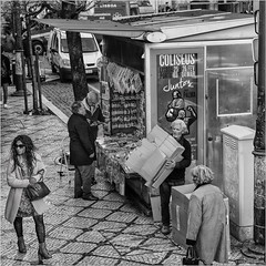 Distracted (John Riper (OFF for awhile)) Tags: johnriper street photography straatfotografie square bw black white zwartwit mono monochrome candid john riper canon 6d 24105 l couple woman man lisbon lisboa portugal people stall kiosk box distraction news stand souvenirs mosaic pavement magazines newspapers bekers cups