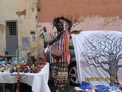 Street Vendors (RubyGoes) Tags: trastevere lazio rome italy carvings men textile black brown pink orange green elephants owls door wheel building blue white tree wood table