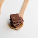Milk Chocolate Pieces in a wooden spoon