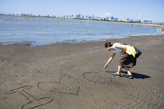 Young woman writing message on beach