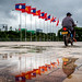 Flags and Motorcyclist, Vientiane, Laos