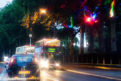 Trees & Lights (M C Smith) Tags: trees green sky lights pentax k3ii red blue orange bus buses car black traffic night headlights taillights fence railings bushes park shadows