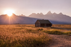 Grand Teton (Ingo Tews) Tags: usa us unitedstates vereingtestaaten wyoming grand teton grandteton grandtetonnationalpark nationalpark sunset sun sonne sonnenuntergang light sunlight licht grass field feld barn scheune mountains berge mountain mormon mormonen natioal park backlight rays old alt house haus building mormonrow homestead jacksonhole