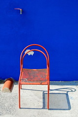 Red Chair Blue Wall (Johan Konz) Tags: red chair shadow blue wall white concretefloor watercrane sewerpipe beachhouse building beach port vada tuscany italy outdoor nikon d90 primary colour beachlife