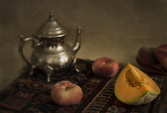 Still Life with Melon and Tea Pot (suzanne~) Tags: stilllife tabletop indoor painterly fruit melon peach teapot texture ethnictextile saddlebag
