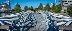2017 - Vancouver - Canoe Bridge (Ted's photos - For Me & You) Tags: 2017 bc britishcolumbia nikon nikond750 nikonfx tedmcgrath tedsphotos vancouver vancouverbc vancouvercity vignetting canoebridge canoebridgevancouver vancouvercanoebridge bridge people peopleandpaths falsecreek falsecreekeast eastfalsecreek scienceworld telusworldofscience dome seawall vancouverseawall railing railings cans2s hff water umbrellas fencing fence citygate citygate1 red redrule