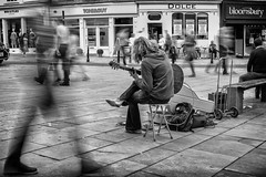 the ghosts and the busker (Daz Smith) Tags: dazsmith fujixt20 fuji xt20 andwhite bath city streetphotography people candid portrait citylife thecity urban streets uk monochrome blancoynegro blackandwhite mono guitar busker music musician performer ghostly