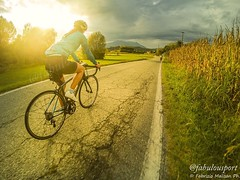 Bike riding as the sunset breaks through the clouds (Fabrizio Malisan Photography @fabulouSport) Tags: goprohero5black gopro italie ciclismosustrada ciclismo biketour cycletouring cycletourism fahrradtour rennrad fahrrad paysage paesaggio landschaft landscape magazine velo nuageux nuages nuvoloso nuvole atmospheric weather warmlight warm september style femme donna woman cycle roadbiking roadcycling road cyclist cycling travel italy biker ride clouds cloudy fitness exercise outside outdoors outdoor lifestyle life bike sunsets tramonto sole soleil sol goldenlight goldenhour light sun sunset