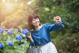 Happy young woman taking picture of hydrangea