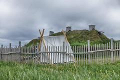 Behind the Fence (gabi-h) Tags: lanseauxmeadows fence fencefriday tent sodhouse vikings newfoundlandandlabrador gabih green grass summer historical wooden clouds sky
