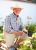 Portrait of a smiling senior with a spade in the garden (ynottri) Tags: 70s activity agriculture break cultivated elderly enjoy enjoyment equipment farm farmer father garden gardener gardening glad grandfather green handsome happy hat herbs hobbies holding joy joyful leisure lifestyles looking male man outdoor pensioner people person recreational relax retired retirement satisfaction senior shovel smile spade straw summer toothy vegetables wisdom working wrinkled