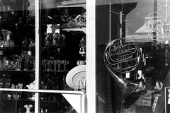 Antique Store Window (bac1967) Tags: ilford panf film 35mm 135 35mmfilm ilfordpanfplus50 panf50plus panf50 blackandwhite blackandwhitefilm blackwhite bw monochrome monotone beerenol beerol beer beerfilmdeveloper caffenol portorchardwa marina sinclairinlet sinclair pugetsound pnw pacificnorthwest washingtonstate washington wa window horn frenchhorn antique antiquestore kingregulacitaiii king regula cita iii rangefindercamera rangefinder steinheilmunchencassar steinheil munchen cassar steinheilmunchen gossenlightmeter gossen