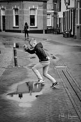 Boy jumps over puddle (PaulHoo) Tags: kampen netherlands holland nikon d700 2017 city urban candid streetphotography bw blackandwhite monochrome kid child jump play puddle street nike