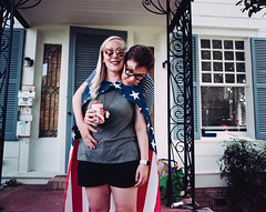 Ann & Erik (BurlapZack) Tags: pentax6x7 smcpentax55mmf4 kodakportra400vc film analog dallastx oakclifftx fourthofjuly july4th independenceday party barbecue bbq grill merica flag cape flagcape couple portrait 120film mediumformat filmisnotdead grainisgood expiredfilm hug cute cuties beer koozie wideangle bokeh dof porch house houseparty friends sunglasses summer summertime