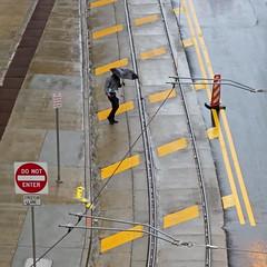 bracing for the crosswind (jim_ATL) Tags: man umbrella wind rain street yellow transverse traffic markings atlanta tropical storm irma