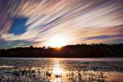 Holes in the Sky (Matt Molloy) Tags: mattmolloy timelapse photography timestack photostack movement motion summer colourful sky sunset clouds trails lines trees water reflection lilypads sun light cranesnestlake burnthills ontario canada landscape nature lovelife