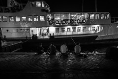 the four musketeers / breathe the night in (Özgür Gürgey) Tags: 2017 20mm bw d750 darkcity karaköy nikon voigtländer candid conversation evening ferry fishing grainy lowlight street vignette istanbul