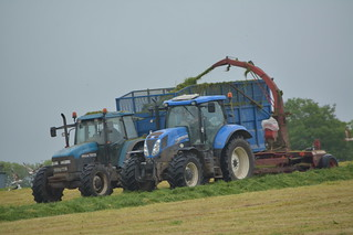 New Holland T7.200 Tractor with a JF Stoll Trailer Forage Harvester filling a Thorpe Trailer drawn by a New Holland TM135 Tractor