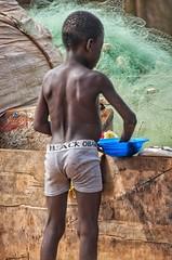 Black Obama underpants (Pejasar) Tags: boy child fishery fishingnet elmina ghana westafrica shirtless blackobamaunderwear bluebowl woodenfishingboat fabric