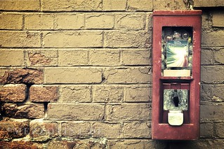 Old gumball machine on ragged brick wall