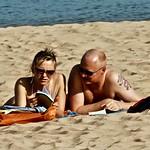 Couple reading at the beach thumbnail