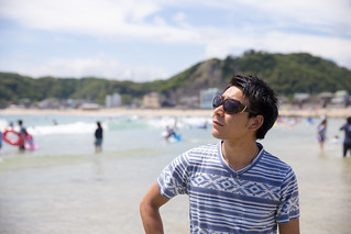 Young man with sunglasses standing on beach